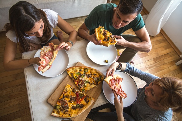 Group of people eating pizza.